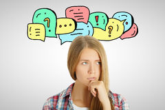 Communication concept. Thoughtful young girl with speech and thought bubbles. Communication concept Royalty Free Stock Images