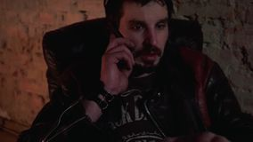 Man in leather jacket speaks on the phone sitting in a leather armchair. Communication devices and technology hardware stock footage