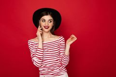 Coquettish young girl talking by mobile phone stock images