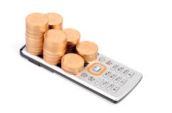 Communication expense. Mobile phone and coins on white background Royalty Free Stock Photography