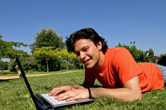 Communication freedom. Smiling young man lying in the grass and working with his laptop Stock Photos