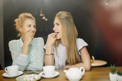 Two women drinking and talking in cafe while having a good time stock photos