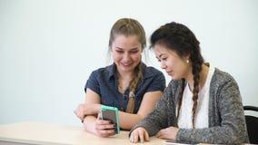 Communication friendship girls using mobile phone. Communication friendship. online social network addiction. teen school girls sitting in a classroom talking stock video