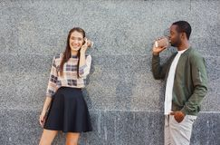 Multiracial couple talking through tin can phone. Communication and fun. Young multiracial couple talking through tin can phone, standing outdoor, copy space Royalty Free Stock Image