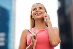 Happy smiling woman calling on smartphone in city Royalty Free Stock Photos