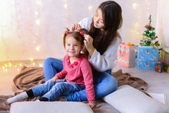 Communication of older female sister with youngest girl sitting. Beautiful girl and elder sister of small female child cares for younger sister and talks, hugs Stock Photography