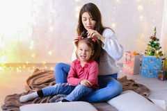Communication of older female sister with youngest girl sitting. Beautiful girl and elder sister of small female child cares for younger sister and talks, hugs Stock Image