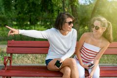Communication between parent and child. Mom and daughter teenager talking and laughing while sitting on the bench in the park Royalty Free Stock Photo