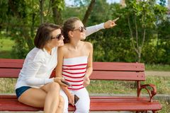 Communication between parent and child. Mom and daughter teenager talking and laughing while sitting on the bench in the park. Mother points with her finger to royalty free stock images