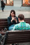 Communication problem man with woman sitting on bench at city street drinking coffee in paper cup looking ito phones stock photo