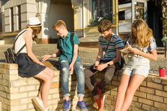 Communication and recreation group of 4 children teenagers. Friends play board game, throwing dice. Background city street royalty free stock photo