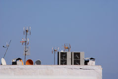 Communication and satellite dishes. Satellite and communication dishes on hotel roof. Air condition units on hotel roof Royalty Free Stock Image