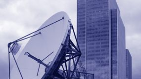Communication satellite and office building. Large satellite dish with corporate building background Royalty Free Stock Photos