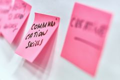 Communication skills written on pink paper stickers attached to a flip chart. Communication skills written on pink and yellow paper stickers attached to a flip Royalty Free Stock Photo