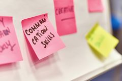 Communication skills written on pink paper stickers attached to a flip chart. Communication skills written on pink and yellow paper stickers attached to a flip Royalty Free Stock Photos