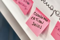 Communication skills written on pink paper stickers attached to a flip chart. Communication skills written on pink and yellow paper stickers attached to a flip Royalty Free Stock Images