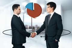Communication and teamwork concept. Handsome european businessman shaking hands in blurry office interior with business pie chart and arrows. Communication and Royalty Free Stock Photos