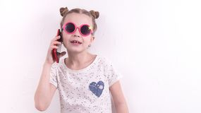 Communication technologies: A girl in pink glasses emotionally talks on the red phone. Portrait at the white wall Royalty Free Stock Image
