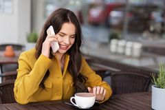 Teenage girl calling on smartphone at city cafe royalty free stock image