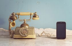 Communication technology. Luxury vintage telephone and smart phone on white wooden classic table royalty free stock photo