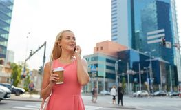 Woman with coffee calling on smartphone in city Royalty Free Stock Photography