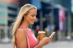 Woman with coffee and smartphone in city. Communication, technology and people concept - happy smiling young woman with coffee and smartphone on city street Stock Photos