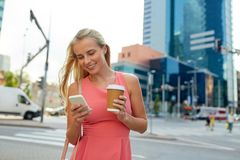 Woman with coffee and smartphone in city Royalty Free Stock Image