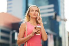 Woman with coffee calling on smartphone in city Stock Image