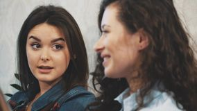 Communication of three young girls in a cafe. Sit on serious topics. Have a sense of humor and long black hair. Slow video stock footage