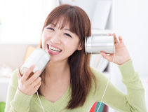 Communication tins. Happy Asian girl using old technology, talk and listen to communication cans. Young woman indoors living lifestyle at home Stock Images