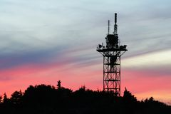 Communication tower. Silhouette on sunset sky Royalty Free Stock Photos