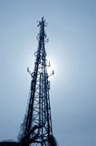 Communication Tower. Silhouette of a communication tower against the glare of sunlight stock photos