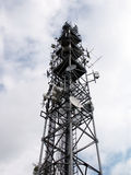 Communication tower. Against a cloudy sky royalty free stock photos