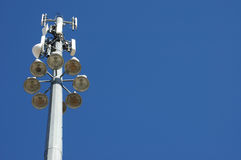Communication Tower. Image of tall communication tower and light pole against deep blue sky Royalty Free Stock Photography