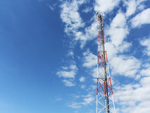 Communication tower against blue sky. Communication tower against partly cloudy blue sky stock image