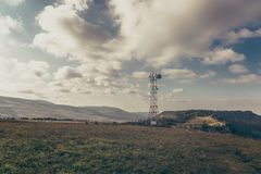 Communication tower antenna on mountain plateau against sky background in alpine terrain Stock Photo