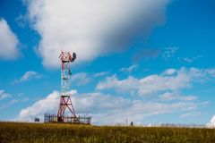 Communication tower antenna on mountain plateau against sky background Stock Photography