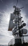 Communication tower backlit against sun Royalty Free Stock Photos