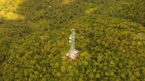 Telephone signal tower among green forest and mountains. Aerial view. Siargao island Philippines. Communication tower, cellphone tower in the jungle in the stock footage