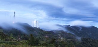 Communication tower with highland apartment in dawn. Morning fogs formation and move downwards to the hill slope created this beautiful waves Stock Photo