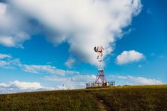 Communication tower for mobile communications and TV antennas on mountain hill at blue sky background. As copy space Stock Images