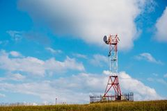 Communication tower for mobile communications and TV antennas on mountain hill at blue sky background. As copy space Stock Photography