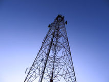 Communication tower at night. Communication tower on blue sky stock photos