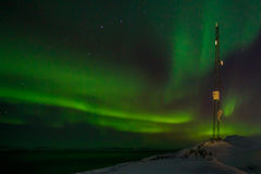 Communication tower and northern lights with a fjord. In the background, Nuuk, Greenland Royalty Free Stock Photo