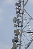 Communication tower and satellite dishes on blue sky background Royalty Free Stock Image