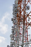 Communication tower and satellite dishes on blue sky background Stock Photos