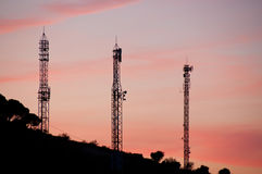 Communication Towers. Silhouettes of communication towers against a sunset Stock Photo