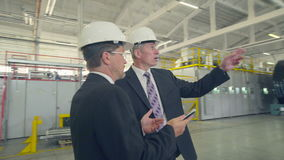 Communication between two businessmen. In factory stock footage