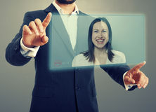 Communication through video chat. Businessman and businesswoman communicating through video chat on virtual device. photo over dark background Royalty Free Stock Photography