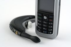 Communications. Mobile phone and headset Royalty Free Stock Photography
